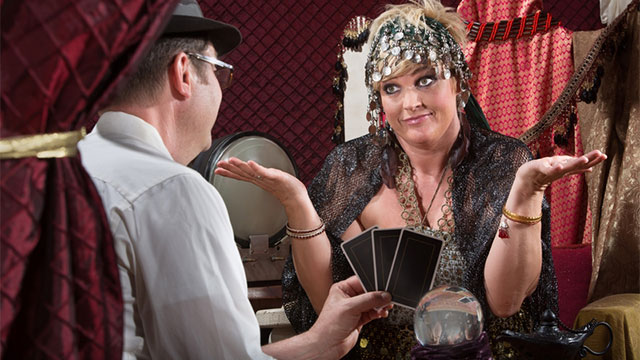 A woman reading tarot for a man wearing a hat.