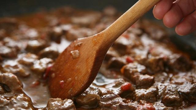 stirring beef stew close up