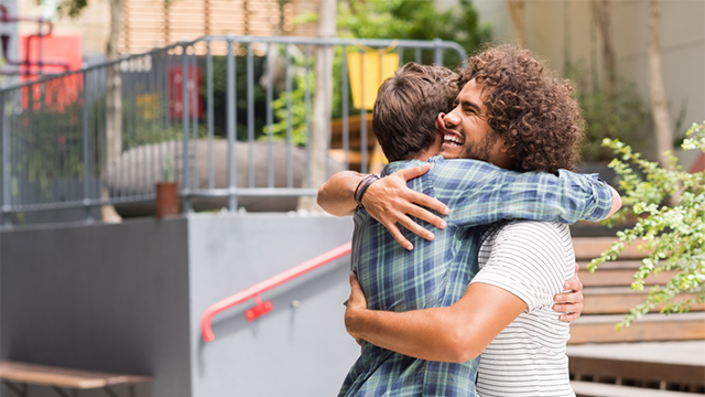 Two young men embrace