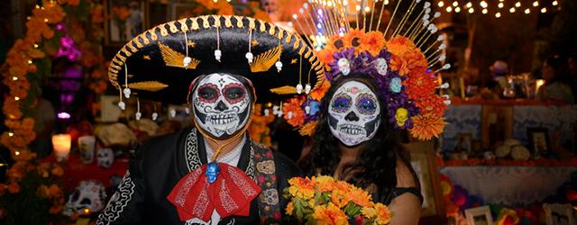 Participants standing in front of an altar during Día de los Muertos.